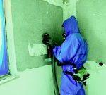 Das Foto zeigt einen Handwerker beim Schleifen einer asbesthaltigen Spachtelmasse